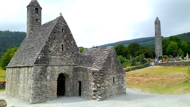 Ancient stone church with a tall tower and graveyard behind in Monastic City, Glendalough, Wicklow, Ireland
