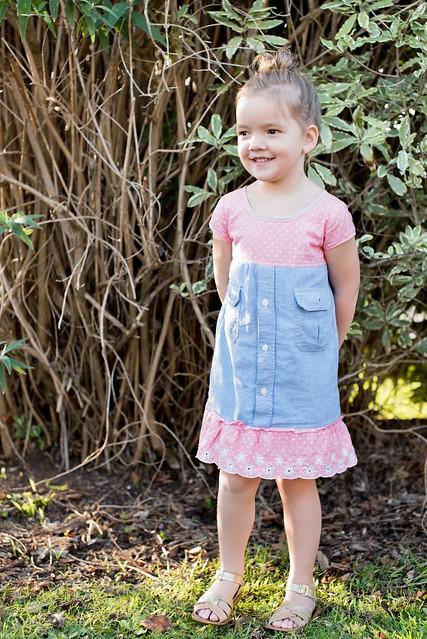 A girl stands in a garden, wearing a handmade dress.