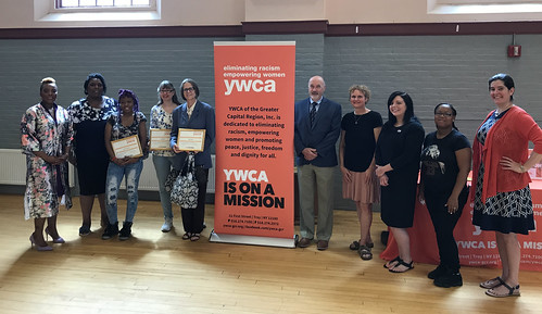 Mayor Madden stands with graduates of the YWCA Ready for Work Program beside an orange YWCA banner which features the mission of the organization