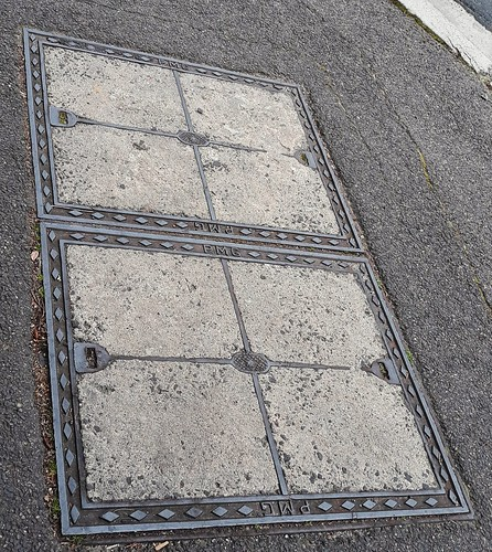 "A concrete and steel access cover in an asphalt footpath, for telecommunication wires. The steel border is stamped ""PMG"", dating it to 1975 or before. Glenferrie Road, Hawthorn, Melbourne, Victoria, Australia."