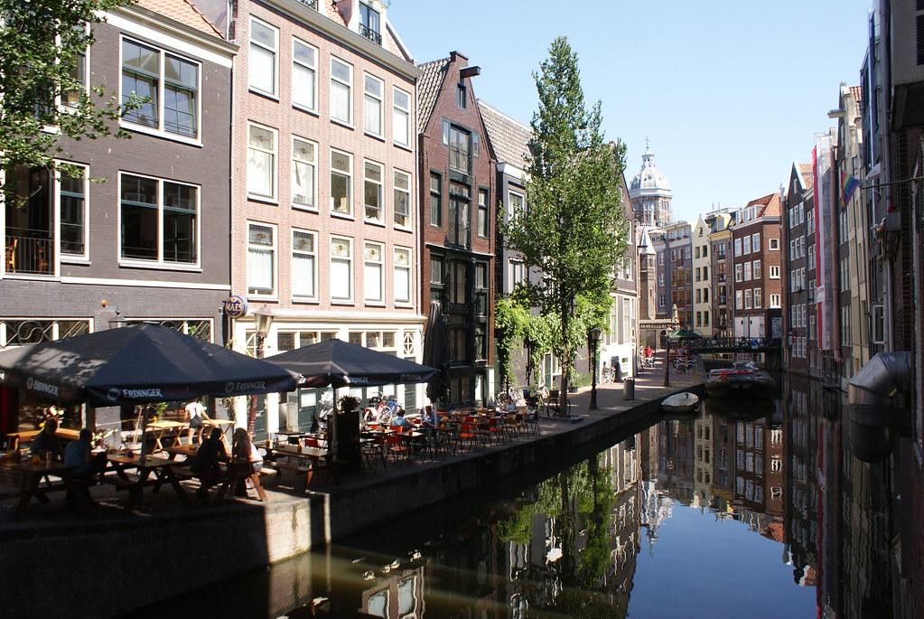 Canal dans le quartier rouge d'Amsterdam avec l'église Saint Nicolas dans le fond.