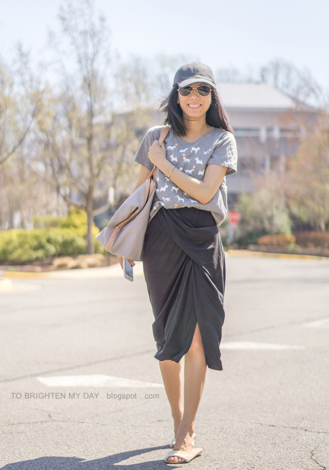 gray wool baseball cap, dog patterned graphic tee, dark gray draped skirt, beige and gray tote, white embellished slides, cuff bracelet