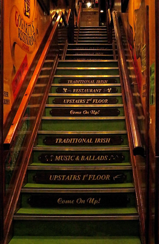 Stairs with an ad for traditional Irish music at the John Gogarty Bar in Dublin, Ireland