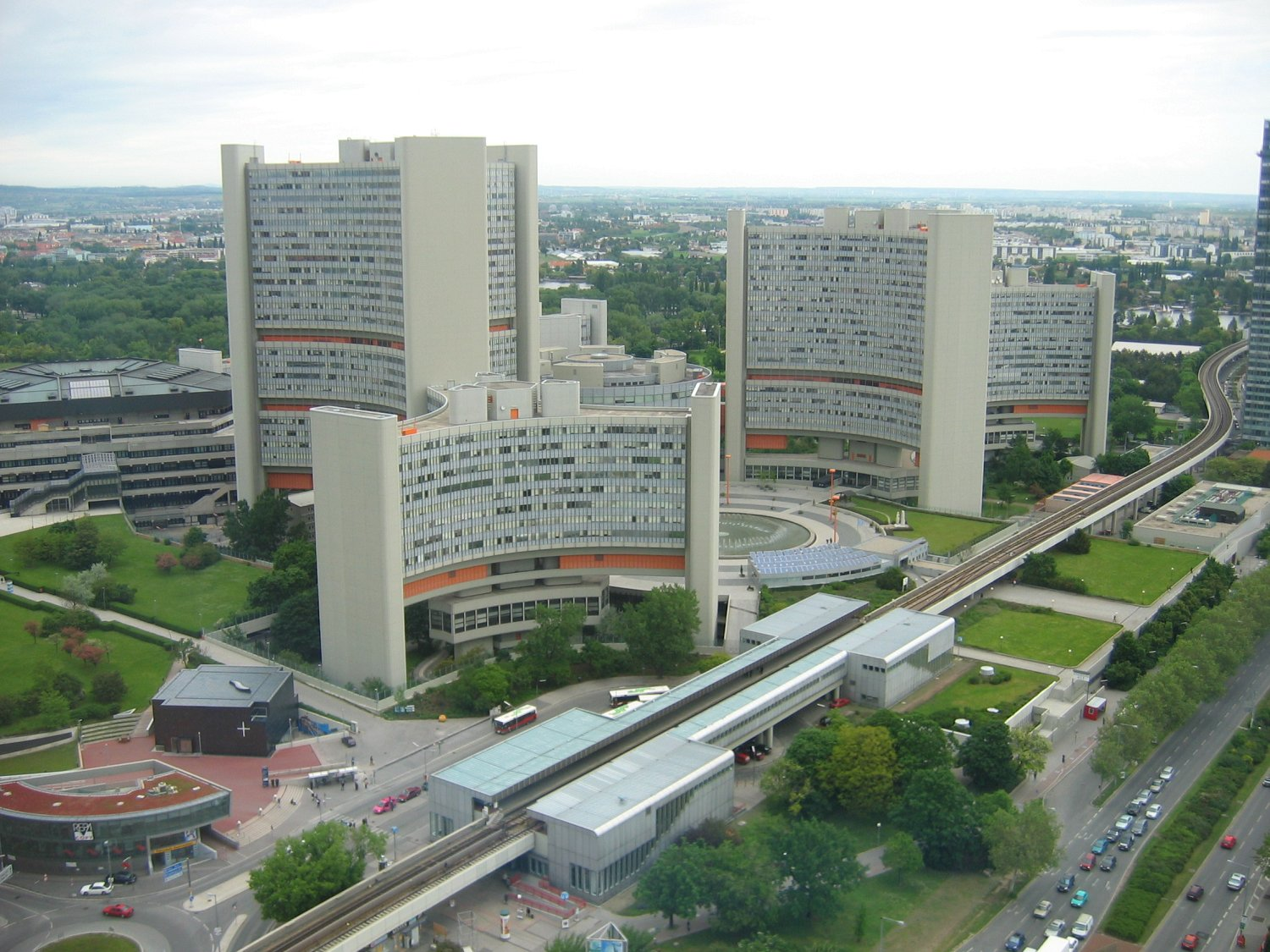 The Vienna International Centre and the Austria Center Vienna (the low hexagonal structure to left of tallest building) are the two parts of the UNO-City. The Donaucity Church (the cubical building in the lower left-hand corner) is part of the Donau City. In the foreground Vienna U-Bahn, Line U1 with station Kaisermühlen – Vienna International Centre. Photo taken on May 17, 2004.