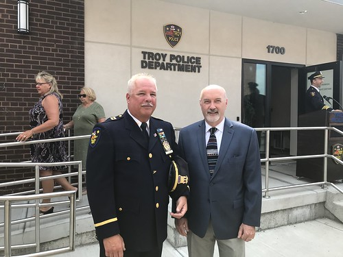 Captain Rick Sprague with Mayor Patrick Madden in front of Troy Police Department headquarters. The Troy Police Department logo is visible on the concrete wall behind Captain Sprague and Mayor Madden