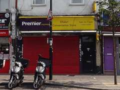"""A terraced shopfront with a red shutter pulled down over it.  Purple and yellow signs above read """"Premier Express"""" and """"Ellalan Convenience Store"""".  A couple of motorscooters are parked outside."""