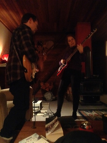 Friends playing guitar at their cabin in the woods