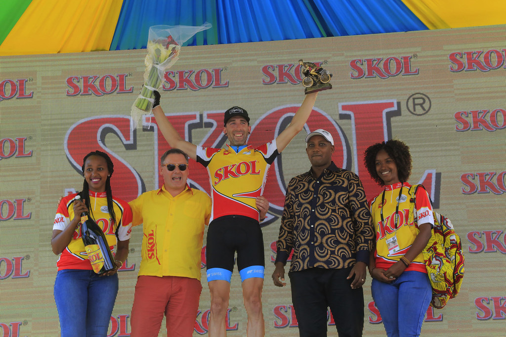 Stage 4 winner Rugg Timothy lifts up the trophy and flowers to celebrate his solo finish in Karongi