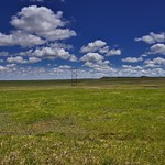 14. Mai 2018 - 12:20 - The story behind this image is that of a drive. I'd just left Badlands National Park and Minuteman Missile National Historic Site earlier that morning and was making the drive up to Theodore Roosevelt National Park. I'd been texting off and on between stops with a friend who was telling me about beautiful beaches t visit, while I responded about the beauty of views of mountains. There were no mountains on this drive between South Dakota and North Dakota, but at this one stop, I had an amazing view looking across this grassy field that seemed to stretch far off into the distance. As a color contrast but also a complimentary one, I had a view to amazing blue skies with these white puffy clouds...what a sight! I thought about cropping some of the foreground to make what I felt was a tighter image, but I decided to keep what I fully captured to let the eyes stare into it and get that wide-eyed feeling that I'd at this roadside stop along South Dakota Highway 79 one early afternoon.