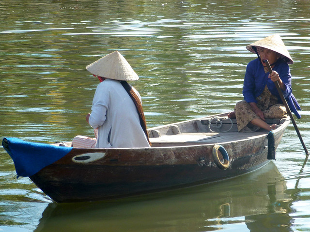 Ladies on traditional Vietnamese boat on the Thu Bon River which flows through Hoi An in South Central Vietnam