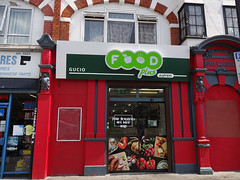 "A ground-floor terraced shopfront painted in a cheerful red, with a large sign above reading ""Food Plus"" in white on bright green and a strapline reading ""Gucio Express"".  The ""o""s of ""Food"" are stylised food items: an apple and a flat bun with steam marks coming off it.  The large glass shop doors have a decal reading ""Your groceries are here!"" and other decals below showing fresh food including sausages, tomatoes, radishes, mushrooms, garlic, red peppers, and a loaf of bread."
