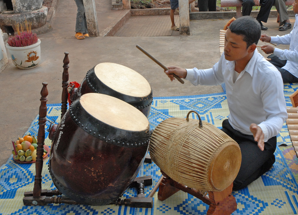 Drummer in a Cambodian pinpeat orchestra simultaneously playing the sideways-mounted skor samphor and double-barreled skor thom.