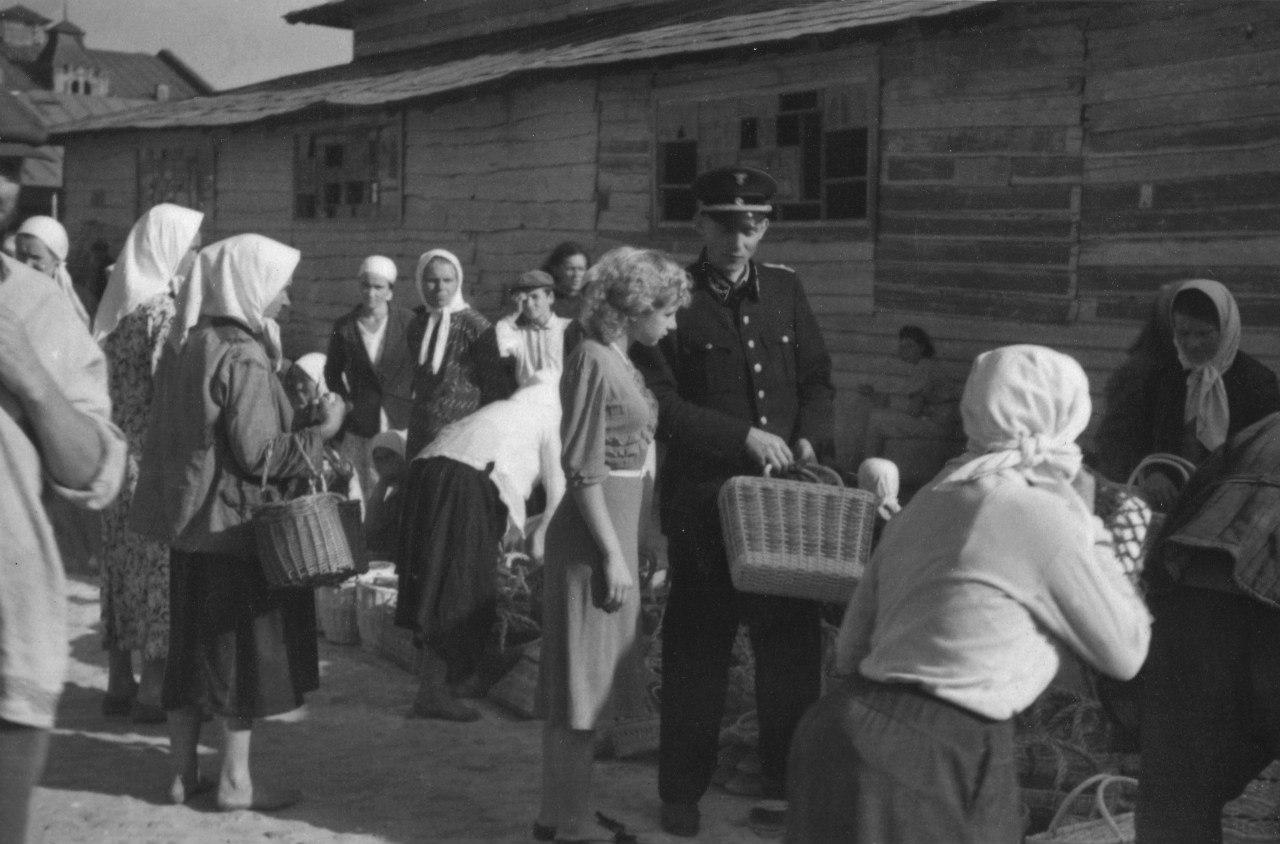 1943. Немецкий железнодорожный служащий (в центре) со своей спутницей (слева) и местные жители на рынке оккупированной Полтавы