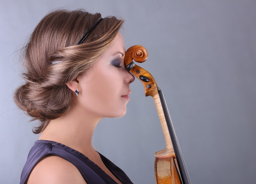 photo of thoughtful violinist with instrument scroll at forehead