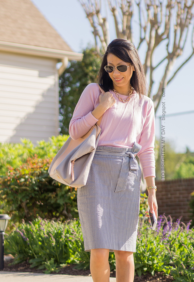 pink sweater, seersucker paperbag pencil skirt with bow tie, beige and gray tote, gold watch