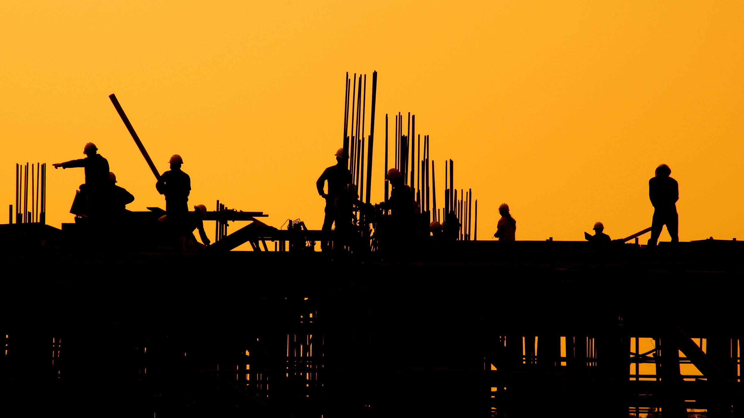 Construction workers silhouetted against the sunset