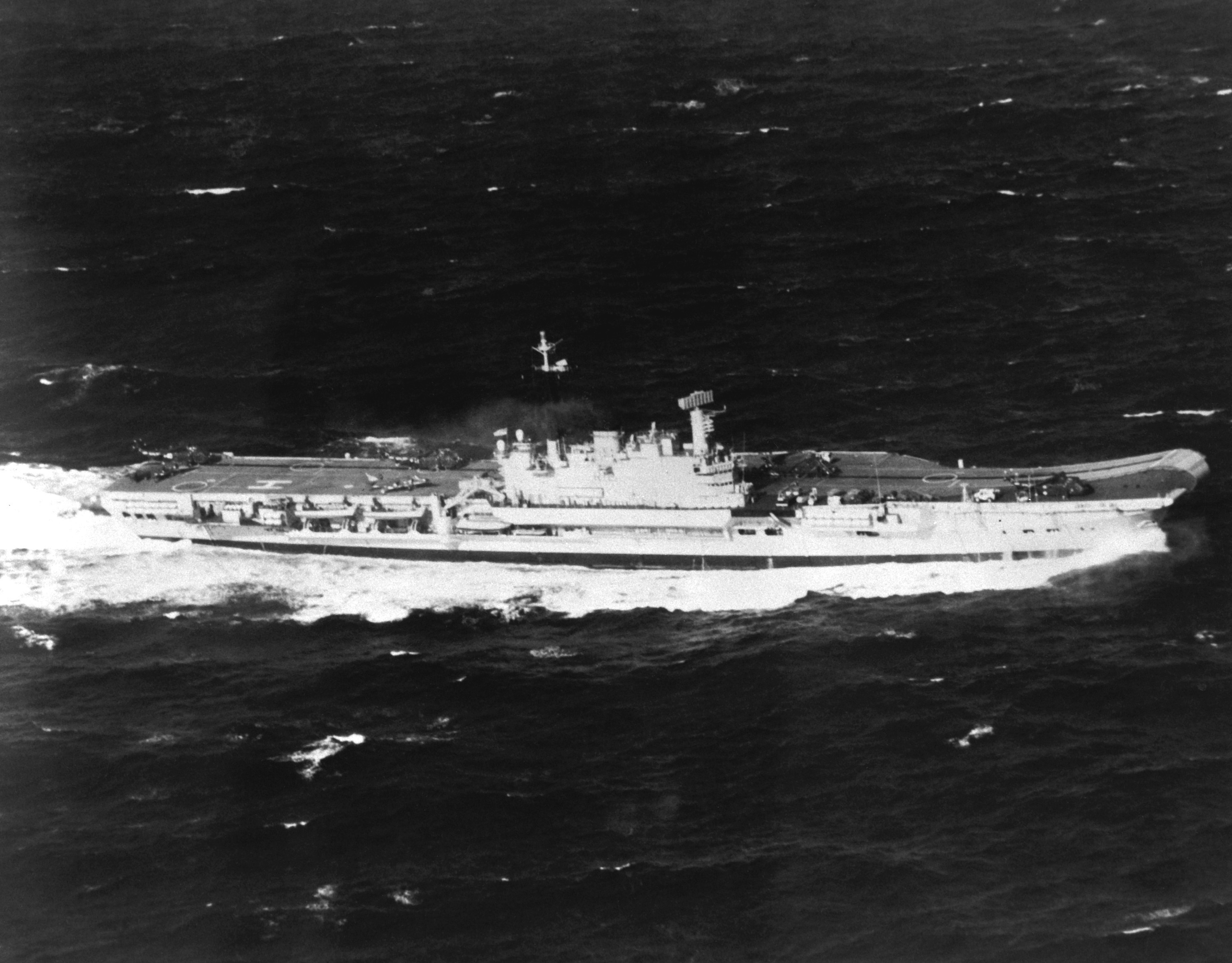 Aerial starboard beam view of the British aircraft carrier HMS HERMES (R-12) underway.