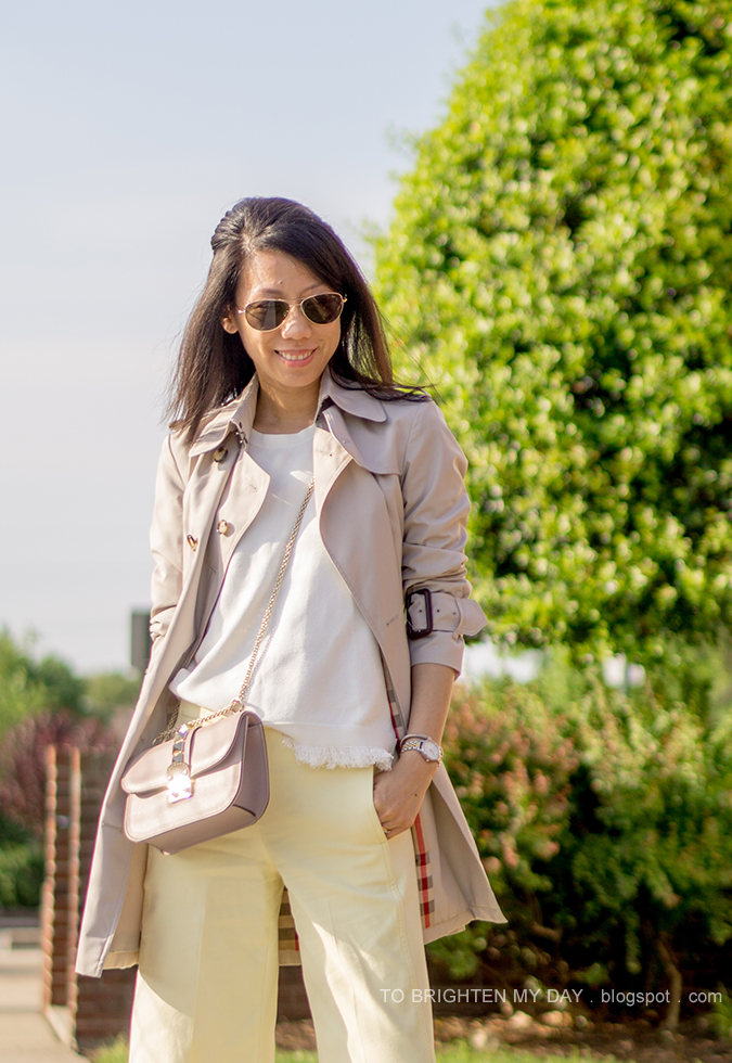 trench coat, white sweater tee, nude crossbody bag, two tone watch, silver cuff, yellow wide leg cropped pants