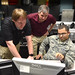 (From the left) Ryan Harris, Air Force Institute of Technology computer system administrator and Barry Mullins, AFIT computer engineering professor, observe 1st Lt. Joshua Mosby, AFIT student, as he explains his computer systems hacking technique during the cyberattack class at Wright-Patterson Air Force Base, Ohio, Feb. 20, 2018. Counter insurgency hacking is an espionage attack weapon used to deter enemy threats to national computer communication systems. (U.S. Air Force Photo by Al Bright/Released)