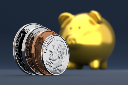 Gold piggy bank with coins on edge