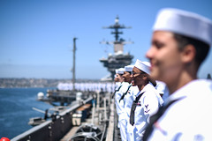 In this file photo, Sailors man the rails as USS Theodore Roosevelt (CVN 71) returns to its San Diego homeport earlier this year.  (U.S. Navy/MC3 Alex Corona)