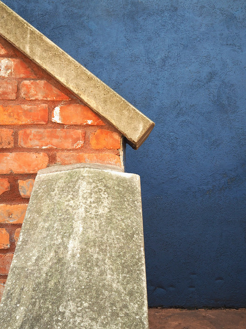 Red brick, white concrete, and blue background