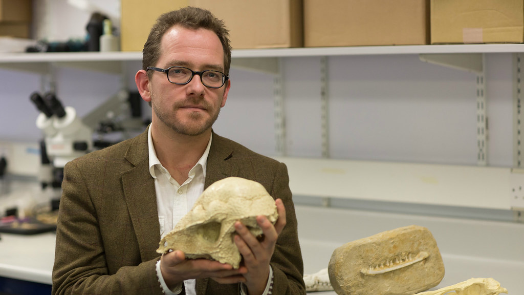 Dr Nick Longrich holding a fossil