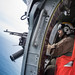 A Sailor mans a .50-caliber machine gun inside an MH-60S Sea Hawk helicopter.