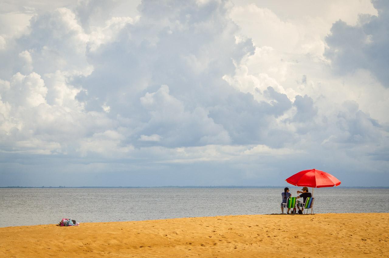 Turistas disfrutan la relajante brisa y la vista del río Paraná desde las dunas de San Cosme y Damián. Las embarcaciones que salen desde la ciudad de San Cosme y Damián, hasta las dunas, tienen una frecuencia de acuerdo a la cantidad de personas que se registran, una vez llegado al cupo de 27 personas, la excursión comienza. Aún así, el territorio es extenso para que los turistas se aíslen y se relajen en el silencio. (Elton Núñez).