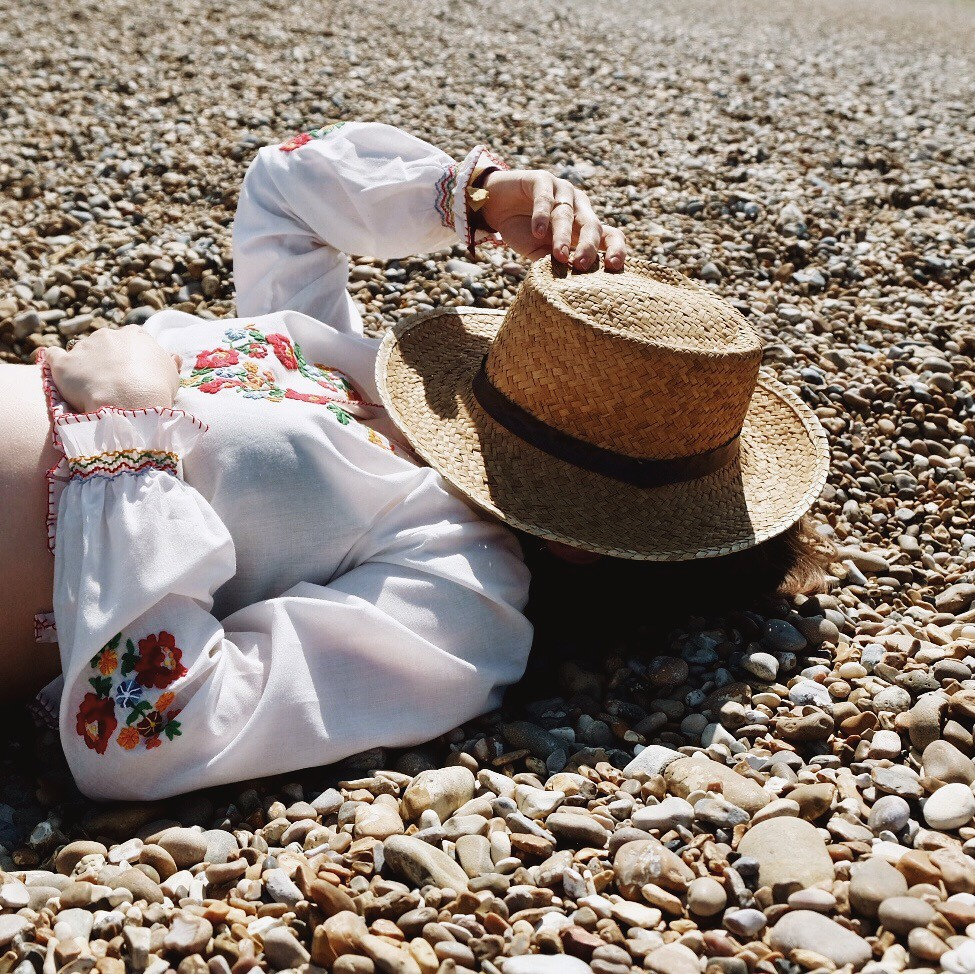 beach woman girl covering face with straw hat