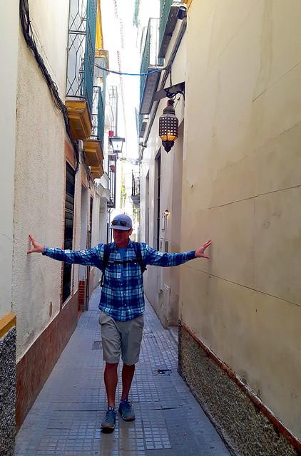 A man touching each side of a narrow alley in Santa Cruz, Seville, Spain