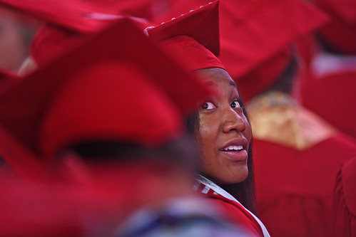 Graduate looks back over her shoulder in search of family in the crowd.