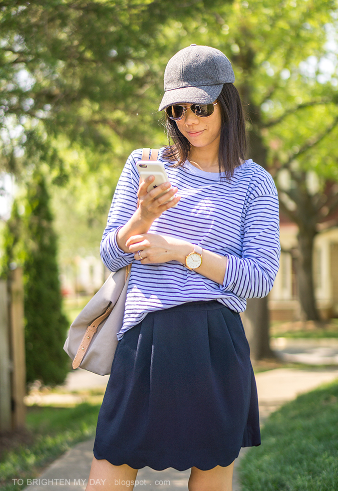 gray wool cap, blue striped top, oversized watch, navy scalloped skirt, beige and gray tote