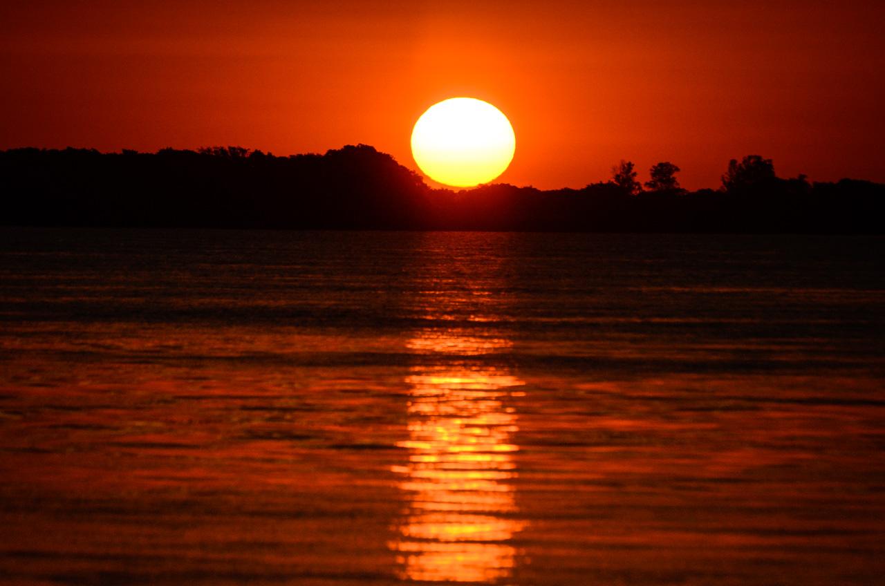 El sol resplandece sus luces naranjas por última vez antes de ocultarse en el horizonte argentino, visto desde la orilla del río Paraguay, en el departamento de Ñeembucú. (Elton Núñez).
