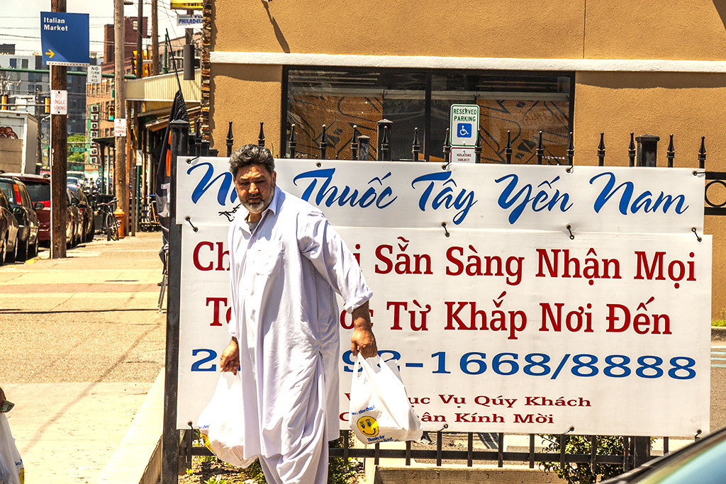 South Asian man in front of Vietnamese sign--Italian Market