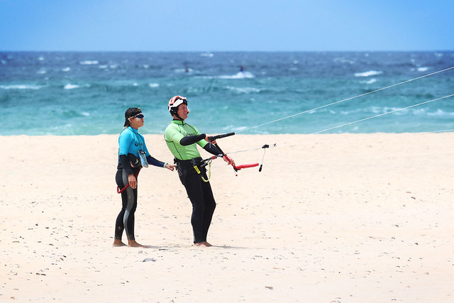 Kitesurfing instructor and student working on kite control on the beach