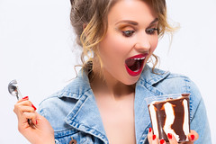 Healhy Food Ideas and Concepts. Exclaiming Caucasian Blond Girl Eating Chocolate Icecream with Dessert Spoon. Posing Against White.