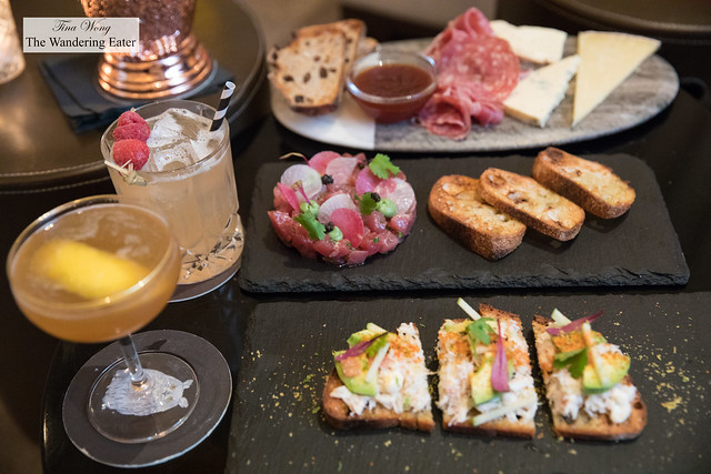 Cocktails and small plates - Crab toast, Tuna tartare, and a board of cheeses and sliced charcuterie
