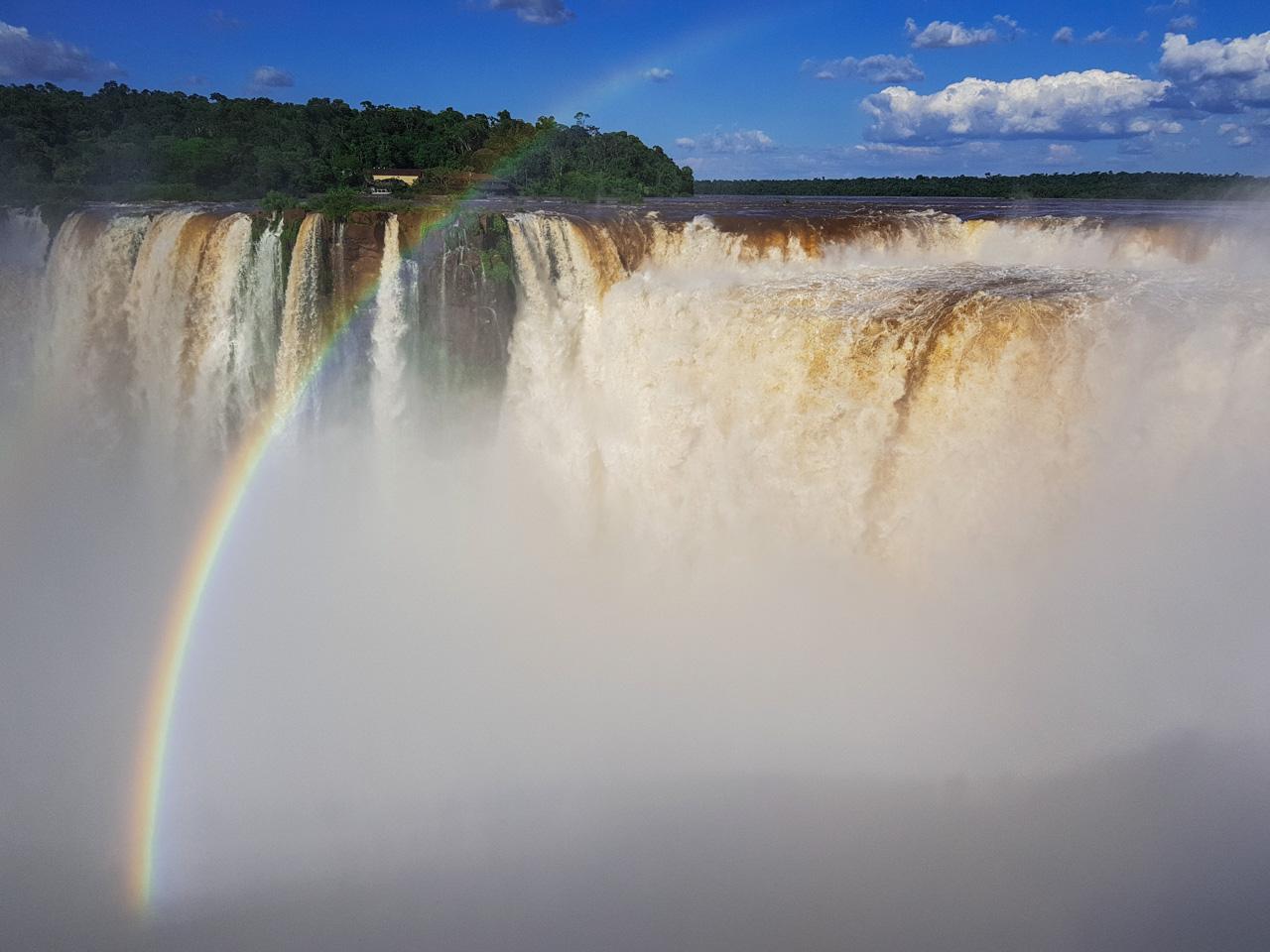 Un arcoíris se revela con el sol de mediodía entre las aguas de las cataratas del Iguazú, en el lado argentino, en Puerto Iguazú - Argentina. Fotografía de smartphone con Samsung Galaxy Note 8. (Elton Núñez).