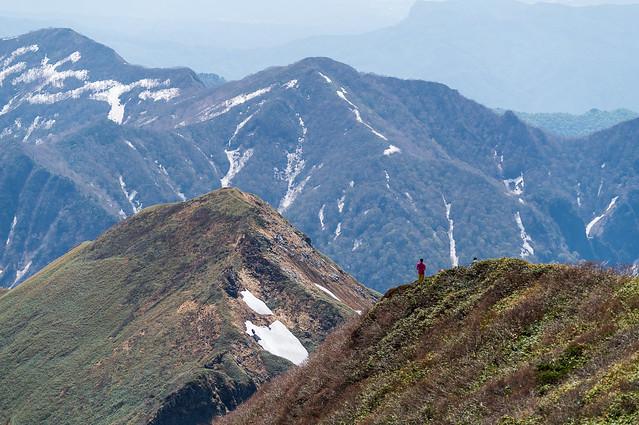 肩に立って展望を楽しむ登山者