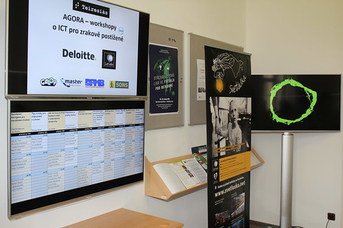 LCD obrazovky s logy partnerů, rozvrhem a prezentacemi Světlušky a Deloitte