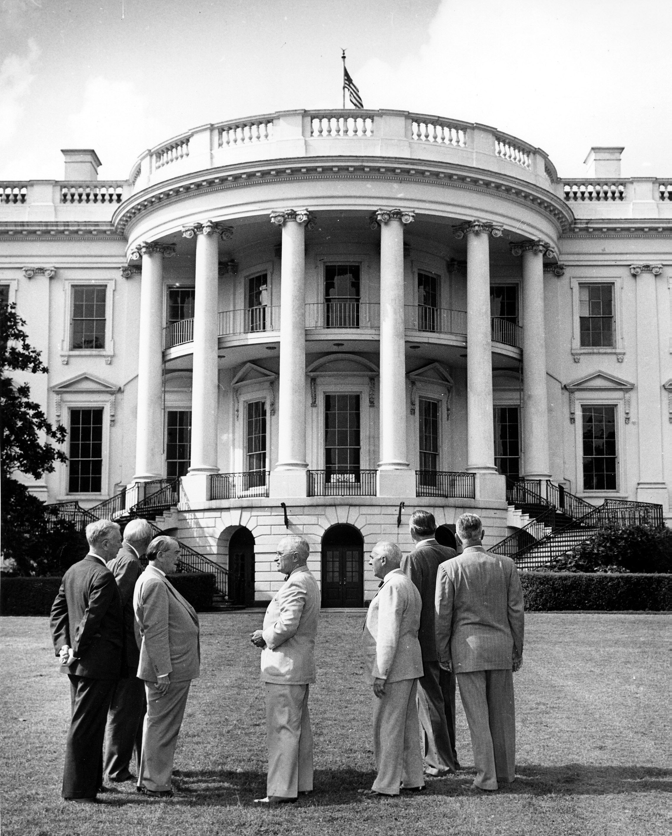 U.S. President Harry S. Truman stands on the lawn of the White House with the Commission on the Renovation of the Executive Mansion on June 20, 1949. From left to right: Senator Edward Martin; Senator Kenneth McKellar; Richard E. Dougherty; President Truman; Douglas Orr, American Institute of Architects; Representative Louis C. Rabaut; Representative Frank B. Keefe. Photo from he holdings of the National Archives and Records Administration, cataloged under the National Archives Identifier (NAID) 6982040.