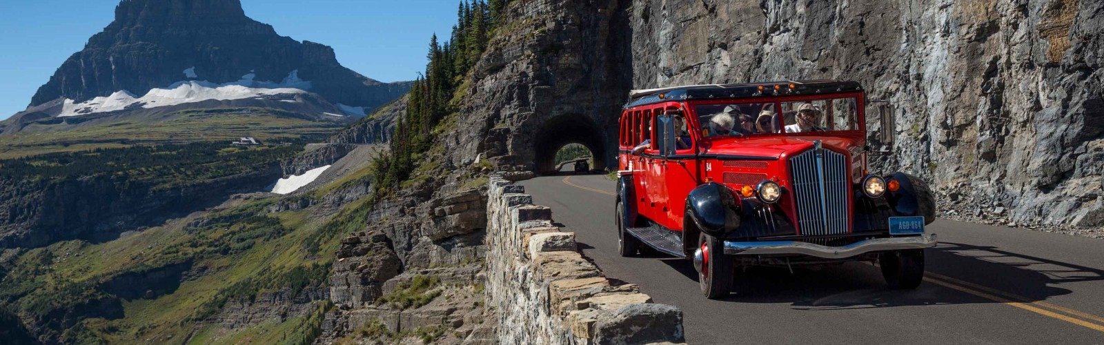 Red Jammer bus travels along Going-To-The-Sun Road in Glacier National Park, Montana.