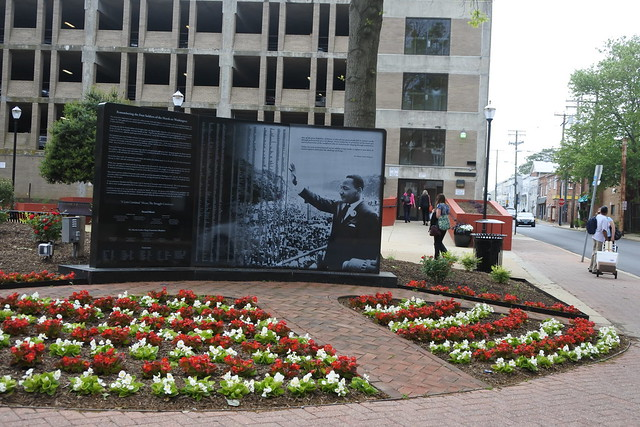 Flower gardens and a brick walkway lad up to granite slabs depicting MLK, a large crowd and a list of names. An office building and street are visible in the background.