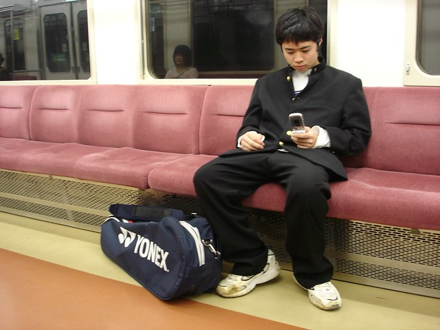 Teen on train. Japanese teenagers are rarely spotted without their