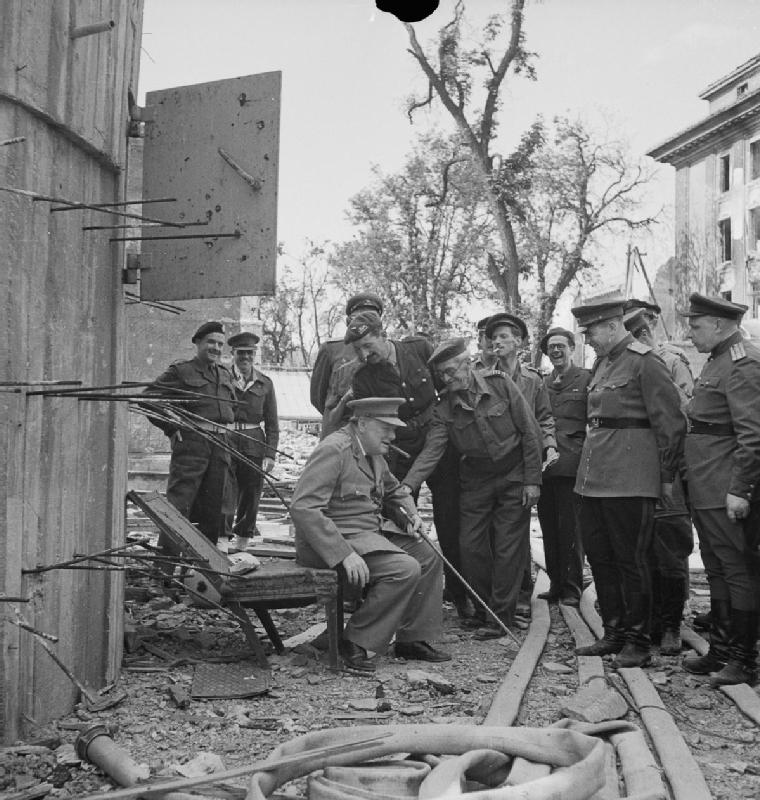 Winston Churchill sits on a damaged chair from the Führerbunker in July 1945.