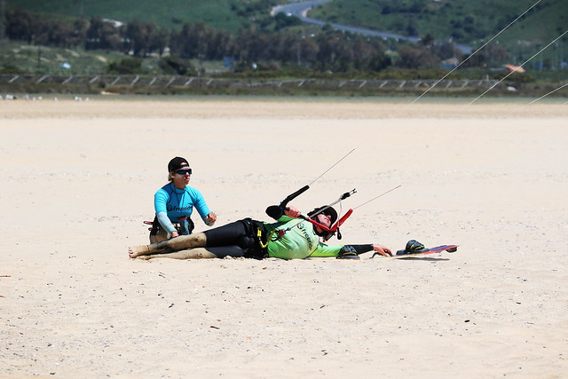 A man laying on the sand with an instructor learning to body drag in a kiteboarding lesson.