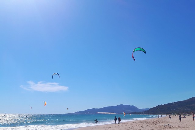 kitesurfing in Tarifa is the most popular thing to do in Tarifa - lots of kites in the sky with blue water and white sand.