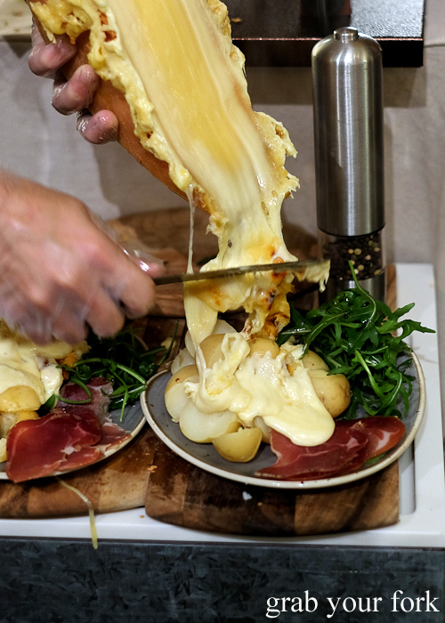 Sliding melted raclette onto potatoes at Raclette Tuesdays at Handpicked Cellar Door in Sydney
