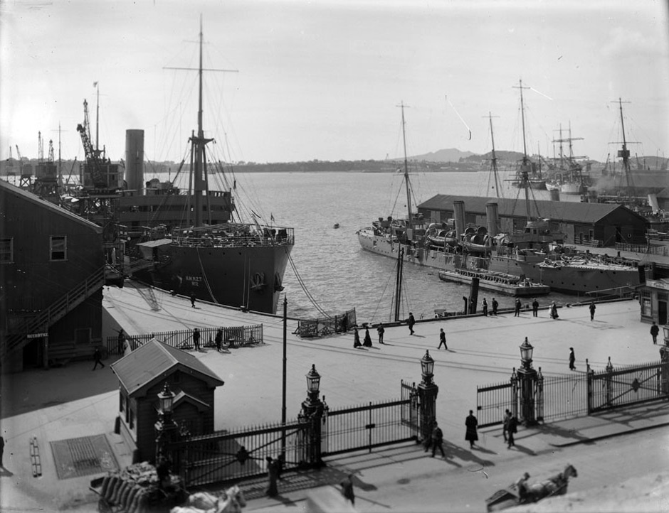 HMS Philomel, New Zealand's first naval ship, is berthed against the Quay Street jetty No. 2 in Auckland. To the left is the troopship Waimana. The ships are preparing for the departure of the Main Body of the New Zealand Expeditionary Force, which sailed from Wellington on October 16 that year.